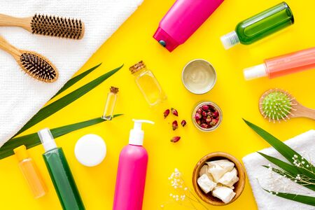 Cosmetic for hair treatment with shampoo, conditioner, styling, oil, comb on yellow background top view pattern