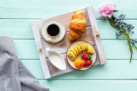 Homemade breakfast on the tray with cup of coffee with cream and fruit on mint green wooden background top view
