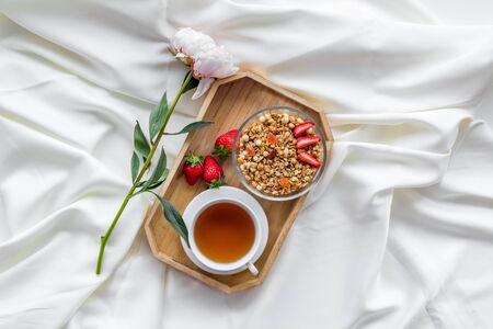 Homemade breakfast on the tray with granola, tea and fruit on white bed sheet background top view Stock Photo