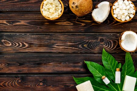 Homemade spa with natural coconut cosmetics on wooden background top view space for text