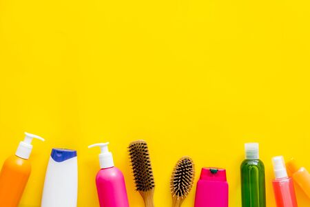 Cosmetic for hair treatment with shampoo, conditioner, styling, comb on yellow background top view mock-up.