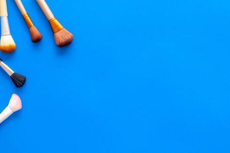 Visagiste work desk. Instruments for make up with brushes on blue background top view mock up