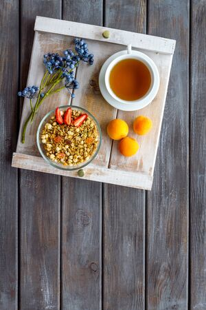 Homemade breakfast on the tray with granola, tea and fruit on wooden background top view mockup Фото со стока