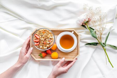 Breakfast on the tray in hands with granola, tea and fruit on white bed sheet background top view