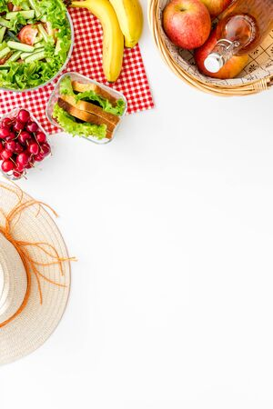 Picnic in summer with products, sandwich, salad, fruits, drinks and hat on white background top view space for text