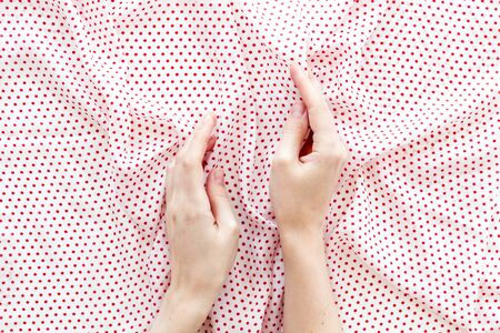 Dotted fabric texture and hands background top view
