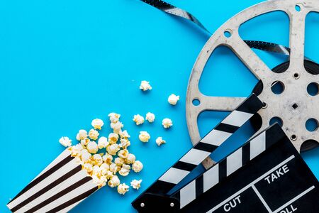 Movie premiere concept. Watch film in cinema with popcorn, video tape and clapperboard on blue background top view