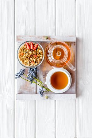 Granola, cup of tea and fruit for homemade breakfast on the tray on white wooden background top view Stock Photo