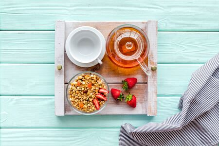 Granola, cup for tea in pot, fruit for homemade breakfast on the tray on mint green wooden background top view