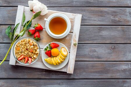 Homemade breakfast on the tray with granola, tea and fruit on wooden background top view mockup Stock Photo