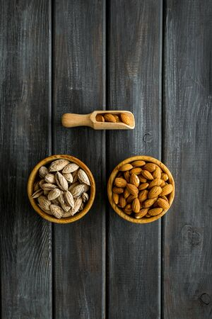 Almond in bowls for cooking on wooden background top view