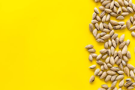 Almond on yellow background top view space for text