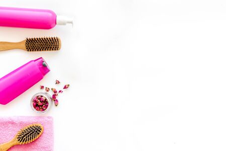 Bottle with shampoo, hair brush for hair style on white background top view mock up