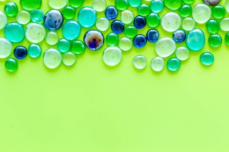 Bright design. Pattern from colored glass stones on green background top view mockup.