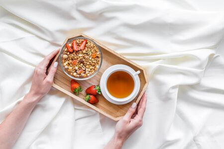Homemade breakfast on the tray in hands with granola, tea and fruit on white bed sheet background top view