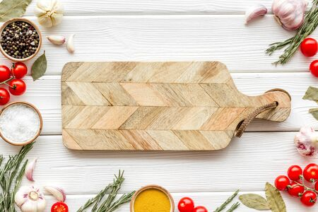Ingredients and cookware. Cutting board in frame of food and spices for chef work on white wooden background top view space for text Imagens