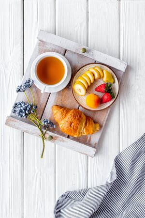 Croissant, tea and fruit for homemade breakfast on the tray on white wooden background top view