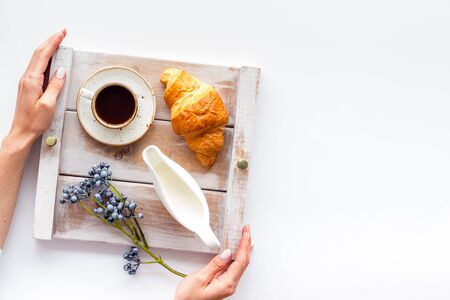 Homemade breakfast on the tray in hands with cup of coffee with cream on wooden background top view mock up