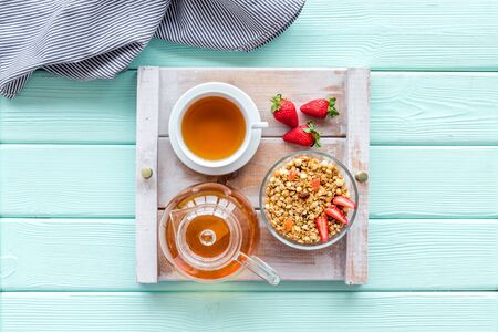 Granola with fruit, cup of tea on tray for breakfast in bed on mint green wooden background top view