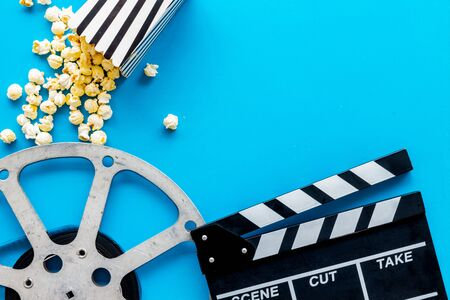 Watch film in cinema with popcorn, video tape and clapperboard on blue background top view Foto de archivo