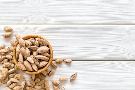 Healthy snack with almonds on white wooden background top view mock up.