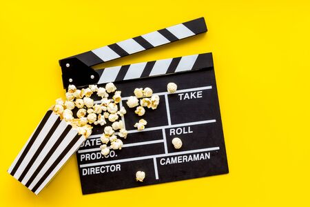 Movie premiere concept. Watch film in cinema with popcorn and clapperboard on yellow background top view