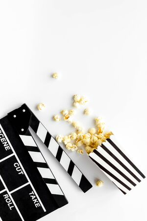 Movie premiere concept. Watch film in cinema with popcorn and clapperboard on white background top view Stockfoto