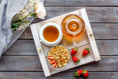 Granola, tea and fruit for homemade breakfast on the tray on wooden background top view Stock Photo