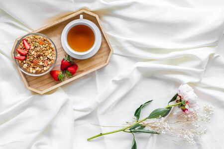 Granola, cup of tea and fruit for homemade breakfast on the tray on white bed sheet background top view