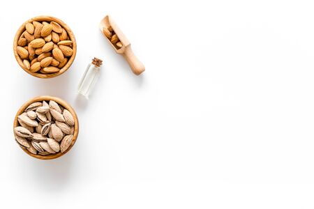Natural seed oil. Almond oil in bottle with almonds on white background top view copyspace