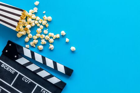 Go to the cinema with popcorn and clapperboard on blue background top view mock up Foto de archivo