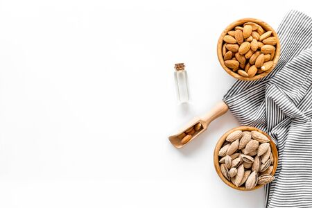 Almond in bowls for cooking oil on white background top view mockup