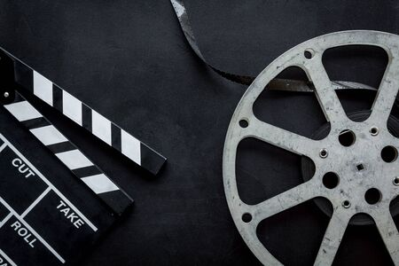 Go to the cinema with film type and clapperboard on black background top view Banque d'images - 127667446