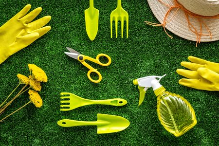 Gardening tools on green grass background top view pattern