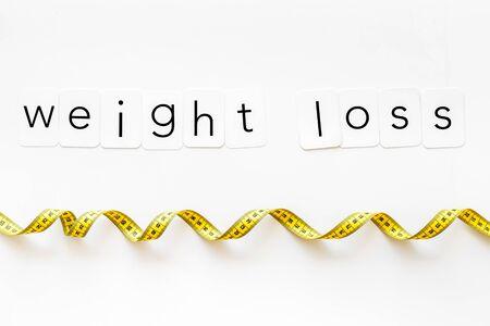 Dieta, fitness e forma del corpo. Testo di perdita di peso con metro a nastro su sfondo bianco vista dall'alto