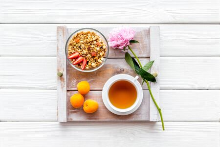 Breakfast on the tray with granola, tea and fruit on white wooden background top view