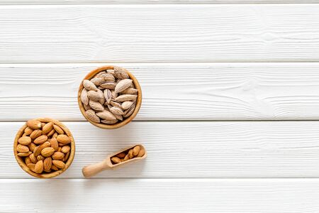 Healthy snack. Almond in bowls for cooking on white wooden background top view mockup Stock fotó