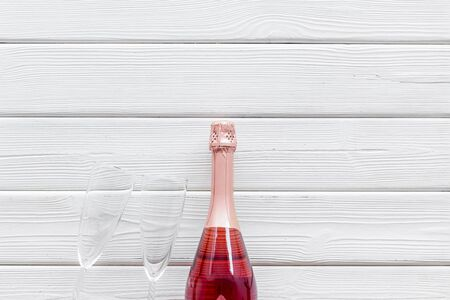 Alcohol for party. Champagne bottle with glasses for celebration on white wooden background top view mockup
