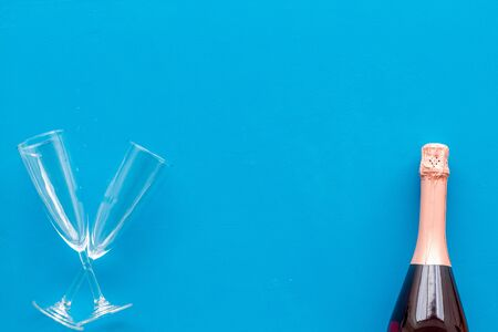 Alcohol for party. Champagne bottle with glasses for celebration on blue background top view mock up
