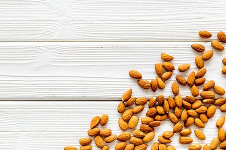 Almond on white wooden background top view space for text