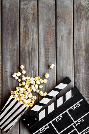 Movie premiere concept with clapperboard, popcorn on wooden background top view space for text