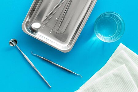 Dentist desk with instruments on blue background top view