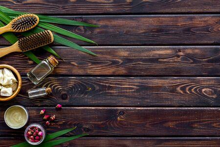 Bottiglia con olio di jojoba, argan o cocco, styling, pettine per acconciatura su fondo in legno vista dall'alto mock up.
