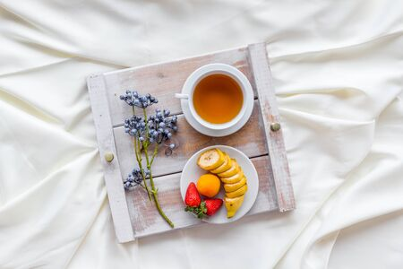 Fruit and tea for homemade breakfast on the tray on white bed background top view