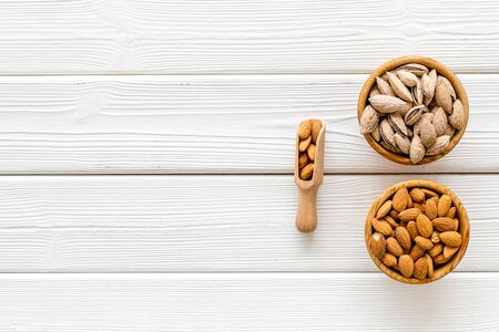 Almond in bowls for cooking on white wooden background top view mockup Stock Photo