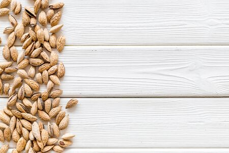 Almond for cooking on white wooden background top view mockup frame