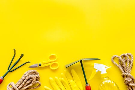 Rake, scissors, spray, rope, gloves. Gardening tools on yellow background top view mockup