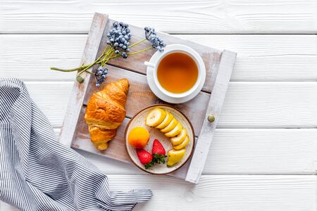Homemade breakfast on the tray with croissant, tea and fruit on white wooden background top view