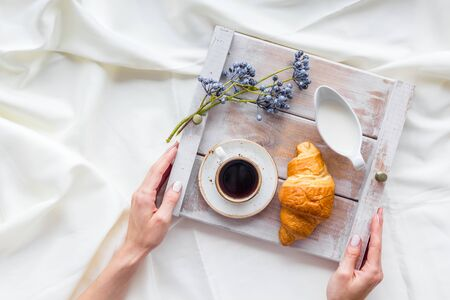 Breakfast on the tray in hands with croissant, coffee with cream on white bed sheet background top view Stockfoto