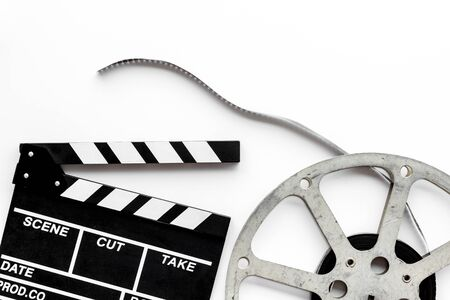 Go to the cinema with popcorn, film type and clapperboard on white background top view Stock Photo